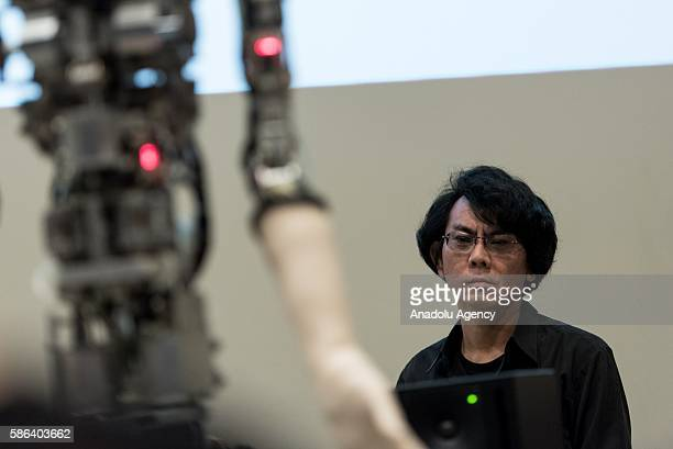 Japanese man looks at the humanoid robot called Alter designed by scientists in Japan as it is exhibited at the National Museum of Emerging Science...