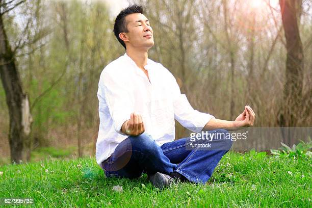 Japanese man meditating in the nature