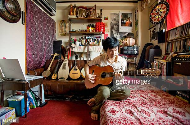 Japanese man playing the guitar in his apartment