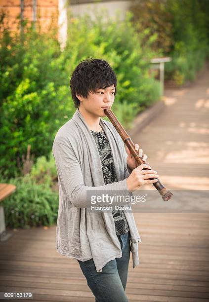 japanese man playing the shakuhachi - bamboo flute stock photos and pictures