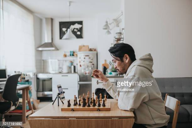 Japanese man playing virtual chess with friend online during social distancing times
