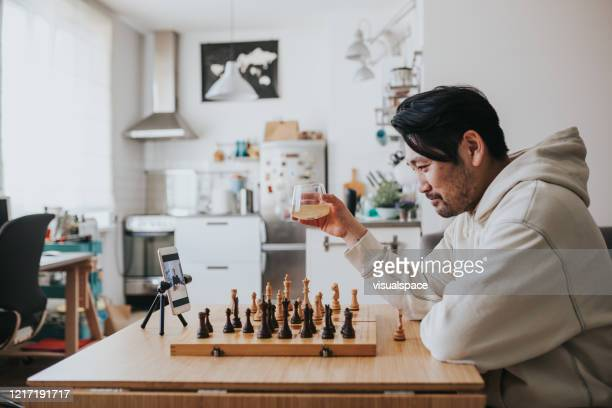 japanese man playing virtual chess with friend online during social distancing times - leisure games stock pictures, royalty-free photos & images
