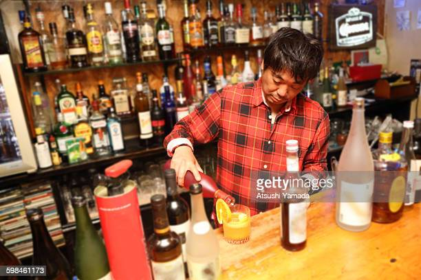 Japanese man pouring drink in bar