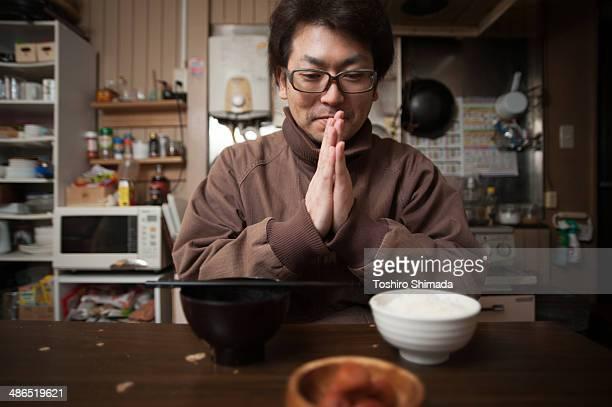 Japanese man praying before eat
