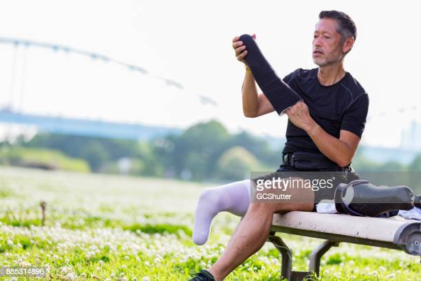 japanese man preapring his prosthetic leg before the routine excercise - old man feet stock pictures, royalty-free photos & images