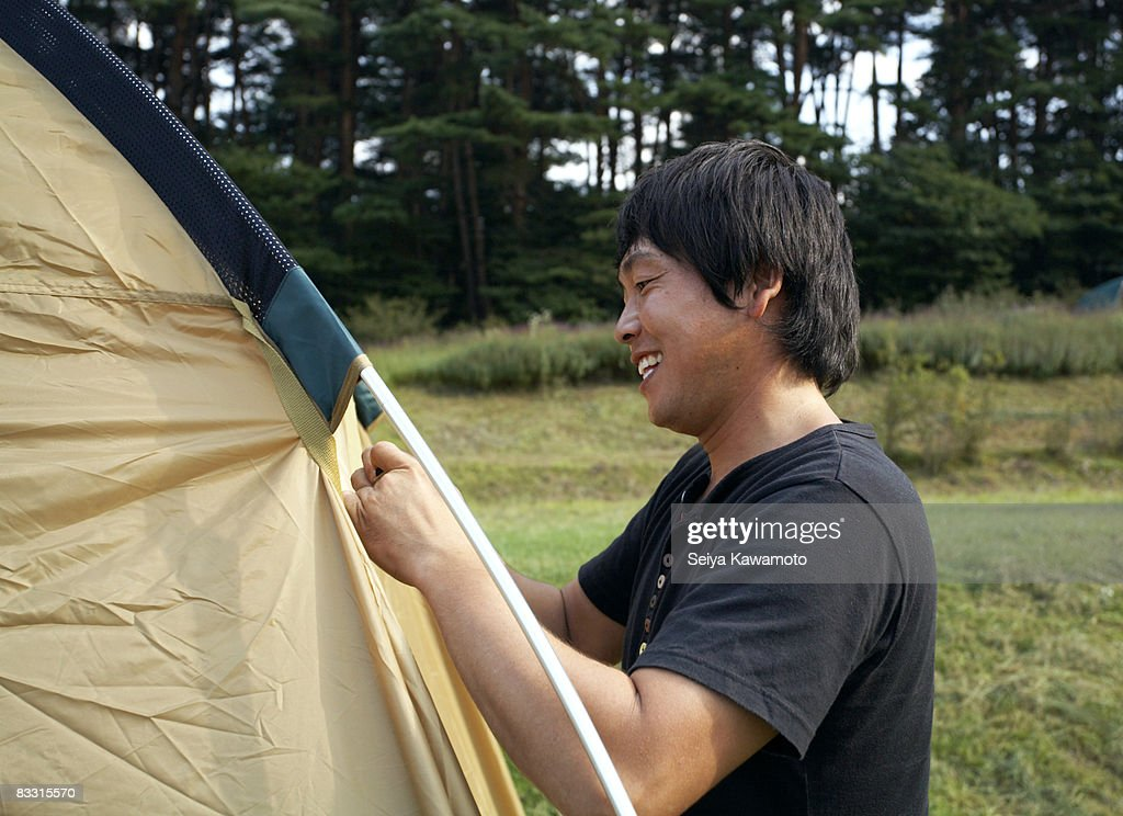Japanese man preparing a camping tent : Stock Photo