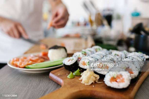 japanese man preparing sashimi and sushi at home - maki sushi stock pictures, royalty-free photos & images
