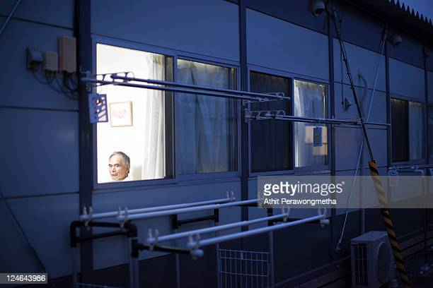 Japanese man rest inside a temporary house built for the victims of the March 11 earthquake and tsunami September 11 2011 in Kesennuma Miyagi...