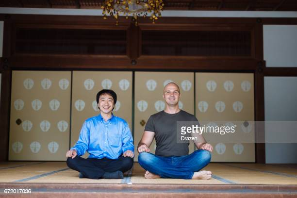 Japanese man showing to European friend how to meditate in shrine