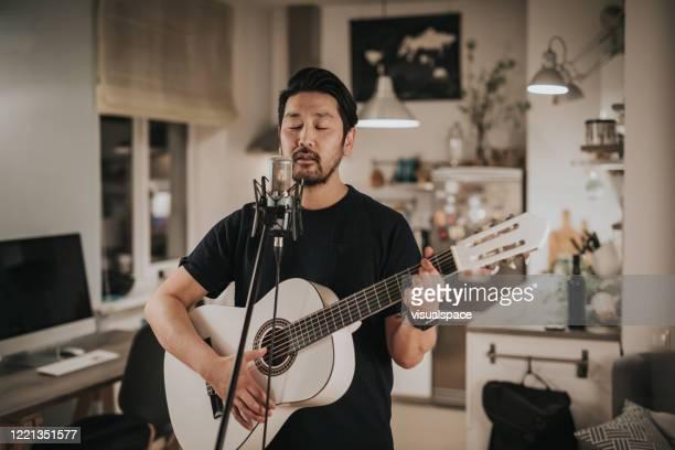 japonês canta e toca guitarra em casa - só um homem - fotografias e filmes do acervo