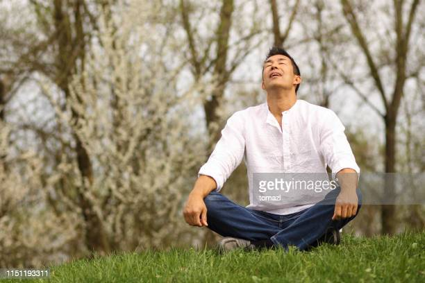 自然の中で座っている日本人男性 - 胡坐 ストックフォトと画像