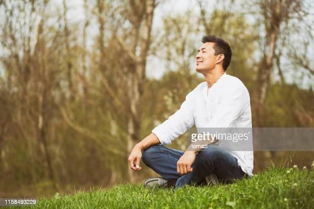 自然の中に座っている日本人男性 - 心の平穏 ストックフォトと画像
