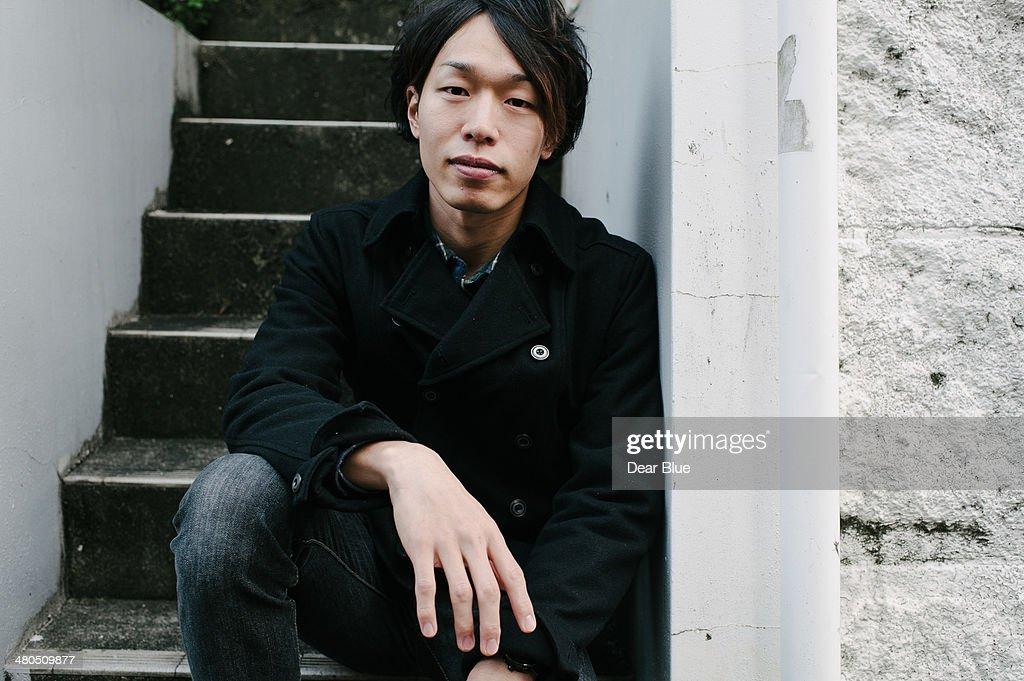 Japanese man sitting on a step : Stock Photo