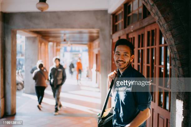 japanese man smiling at camera on street - stubble stock pictures, royalty-free photos & images