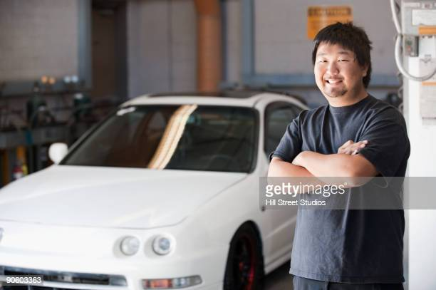 Japanese man standing near car in auto body shop