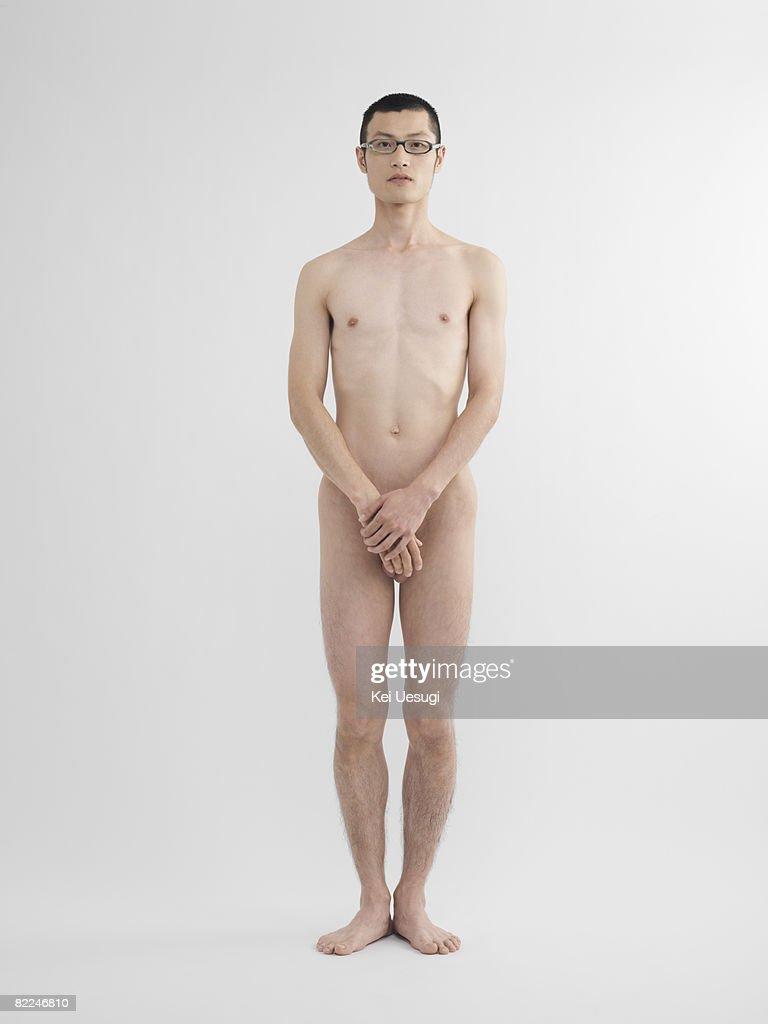 Japanese man standing nude in studio : Stock Photo
