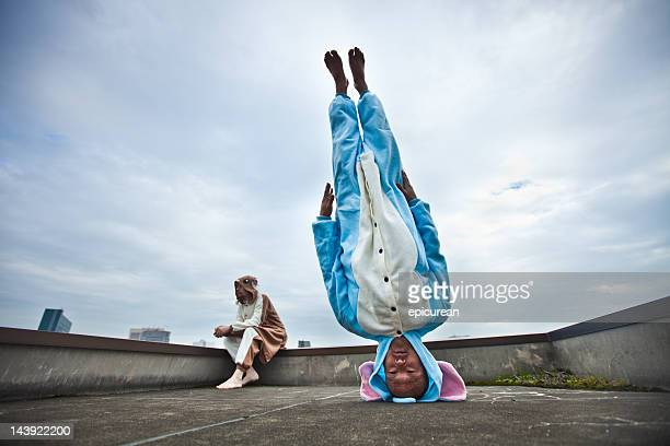 japanese man standing on his head in elephant costume - op z'n kop stockfoto's en -beelden