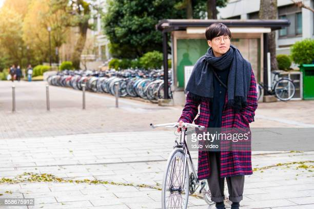Japanese man standing with a bicycle