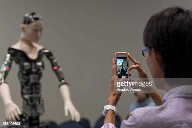 Japanese man takes a photo of the humanoid robot called Alter designed by scientists in Japan as it is exhibited at the National Museum of Emerging...