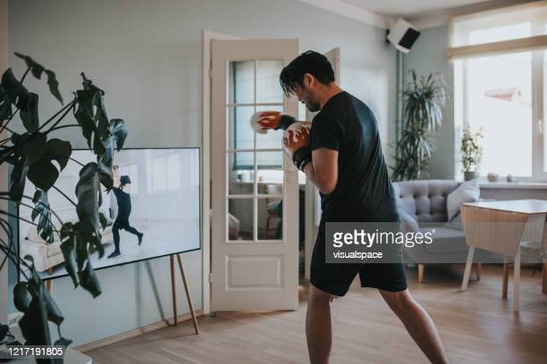 japanese man taking online boxing lessons during lockdown in isolation - boxing stock pictures, royalty-free photos & images