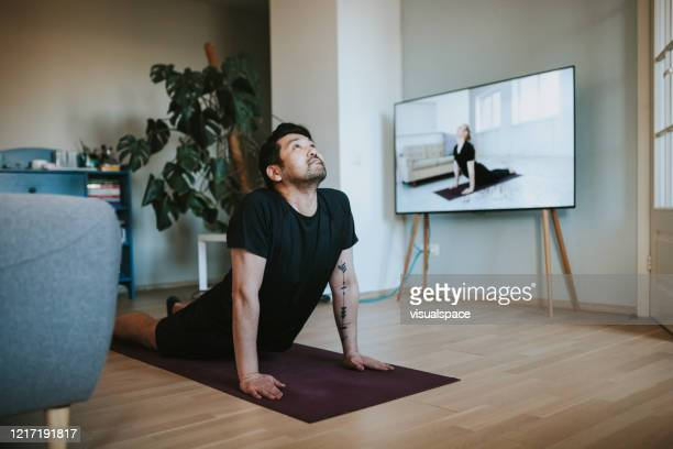 japanese man taking online yoga lessons during lockdown in isolation - exercising stock pictures, royalty-free photos & images