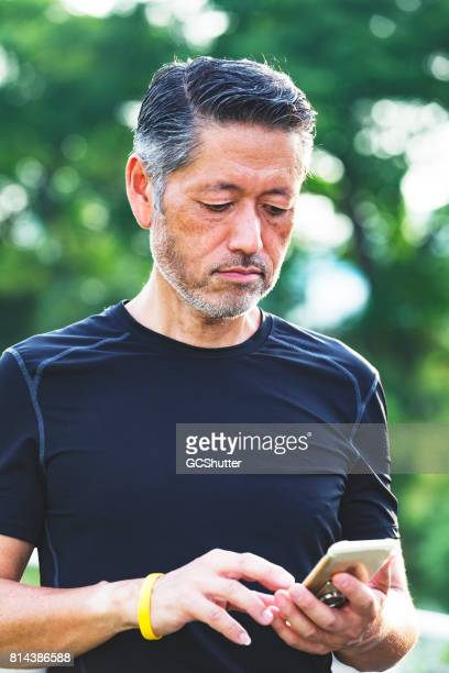Japanese man talking a break from his morning jog to use his smart phone