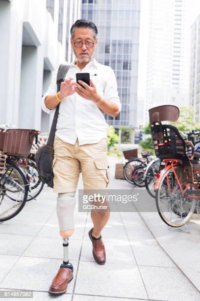 Japans man SMS op zijn slimme telefoon als hij langs een lijn van fietsen loopt