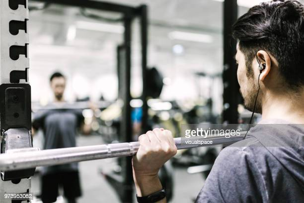 japanese man trains with barbell in the gym - strength training stock pictures, royalty-free photos & images