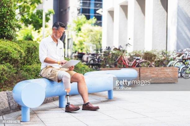 Japanese man using a digital tablet at a public park near some bike stand