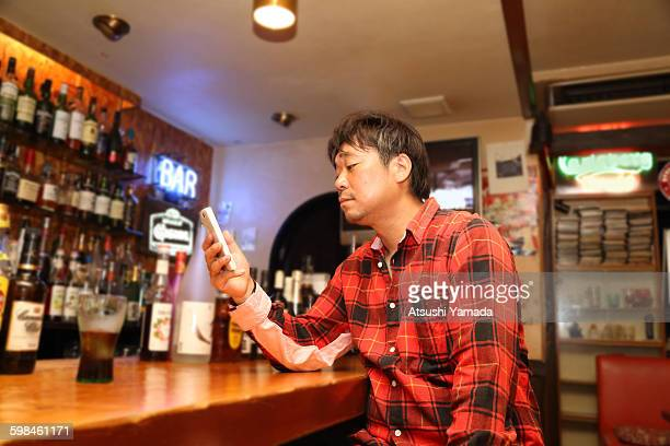 Japanese man using mobile phone in bar