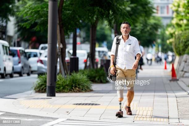 Japanse man lopen richting het zebrapad op een kruising van de weg