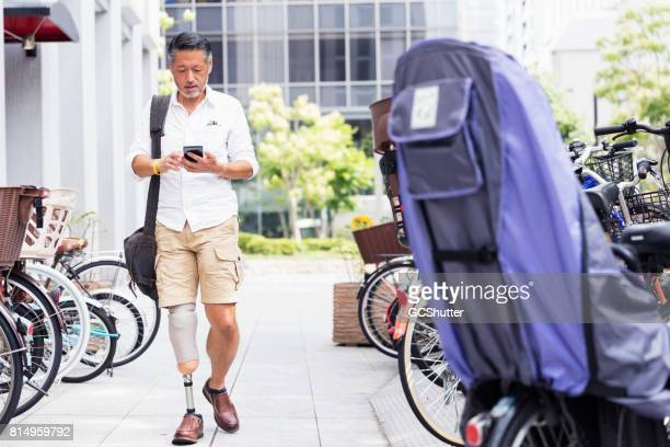 Japanse man lopen tijdens het lezen van een massage op zijn smart phone