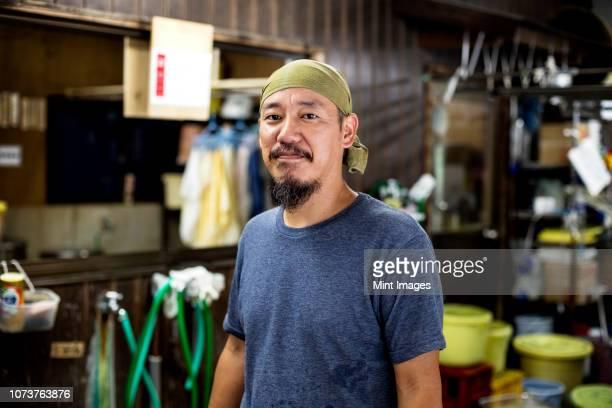 japanese man wearing bandana in a textile dyeing workshop, smiling at camera. - バンダナ ストックフォトと画像