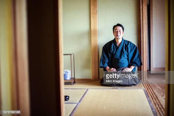 japanese man wearing kimono kneeling on floor, on a tatami mat during tea ceremony. - 着物 ストックフォトと画像