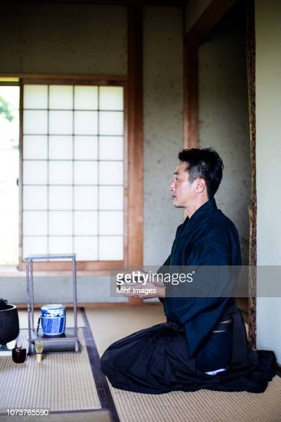 japanese man wearing traditional kimono kneeling on floor, holding tea bowl, during tea ceremony. - ceremony stock pictures, royalty-free photos & images