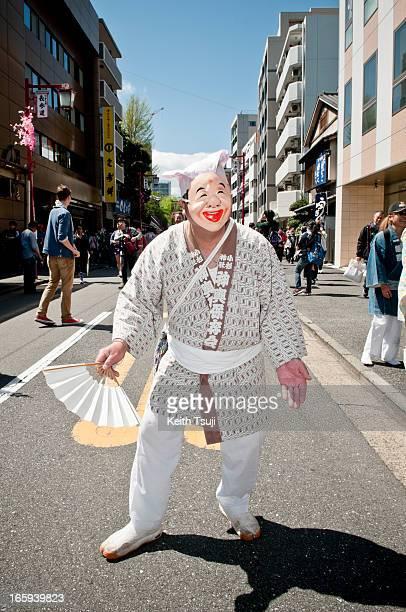 Japanese man wears a face mask as he parades through the streets at Kanamara Matsuri on April 7 2013 in Kawasaki Japan The festival is held annually...