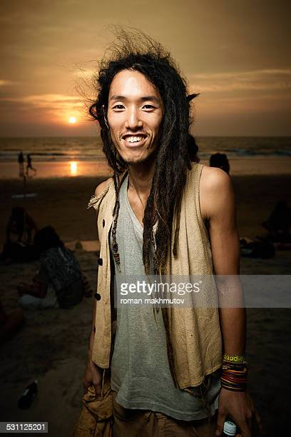 Japanese man with dreadlocks on the beach