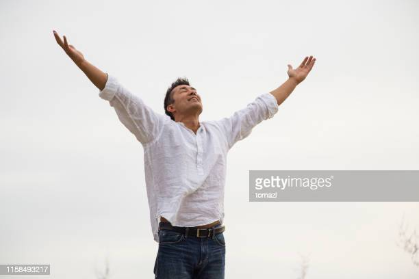 japanese man with hands in the air enjoying life - mental wellbeing stock pictures, royalty-free photos & images