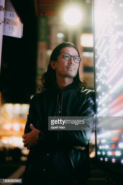 japanese man with long hair and eyeglasses at night in tokyo - un seul homme d'âge moyen photos et images de collection