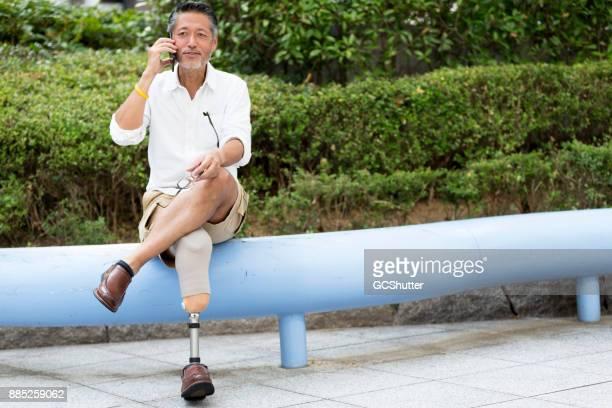 Japanse man met prothetische been zitten buiten zijn kantoor en spreken op zijn mobiele telefoon