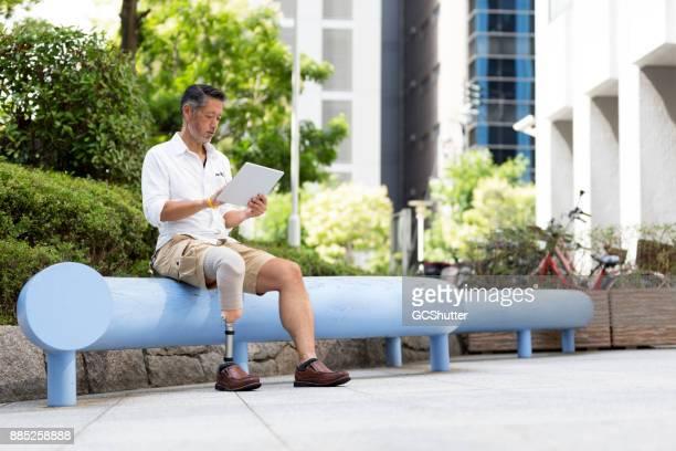 Japanse man met prothetische been zitten buiten zijn kantoor met een digtial tablet