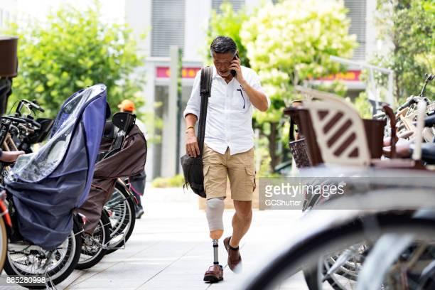 Japanse man met prothetische been wandelen langs de parkeerplaats tijdens het gesprek op zijn mobiele telefoon