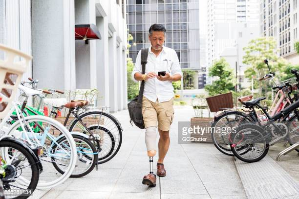 Japanese man with prosthetic leg walking along the parking lot while checking his phone