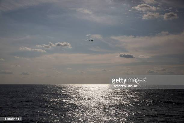 Japanese Maritime Self-Defense Force helicopter flies seen from the bridge of British Royal Navy's HMS Montrose frigate during a joint exercise with...
