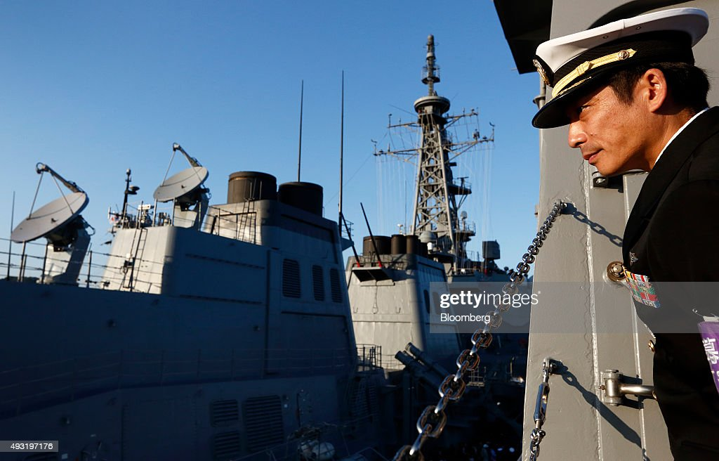 A Japanese Maritime Self-Defense Force officer looks on as the Murasame destroyer vessel arrives at a pier of the Yokosuka Base after a fleet review in Yokosuka, Kanagawa Prefecture, Japan, on Sunday, Oct. 18, 2015. Prime Minister Shinzo Abe's public approval ratings declined after the passage of legislation allowing Japan to send troops to fight in overseas conflicts for the first time since World War II. Photographer: Tomohiro Ohsumi/Bloomberg via Getty Images