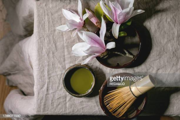 Japanese matcha green tea in craft ceramic cup with bamboo whisk and pink magnolia flowers on grey linen table cloth. Flat lay. Space.