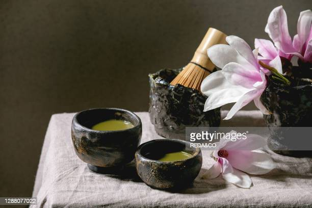 Japanese matcha green tea in craft ceramic cups with bamboo whisk and pink magnolia flowers on grey linen table cloth.