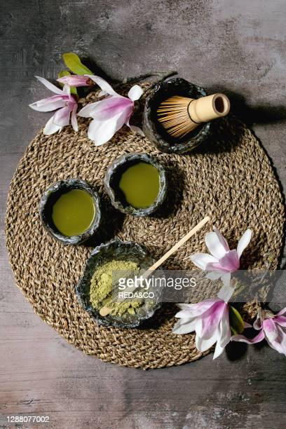 Japanese matcha green tea in craft ceramic cups with matcha powder. Bamboo whisk and pink magnolia flowers on straw napkin over dark texture...