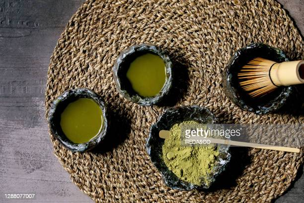 Japanese matcha green tea in craft ceramic cups with matcha powder. Bamboo whisk on straw napkin over dark texture background. Flat lay. Space.