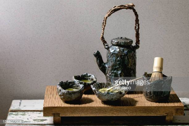 Japanese matcha green tea in craft ceramic cups with matcha powder. Bamboo whisk. Ceramic teapot on traditional wooden japanese table.